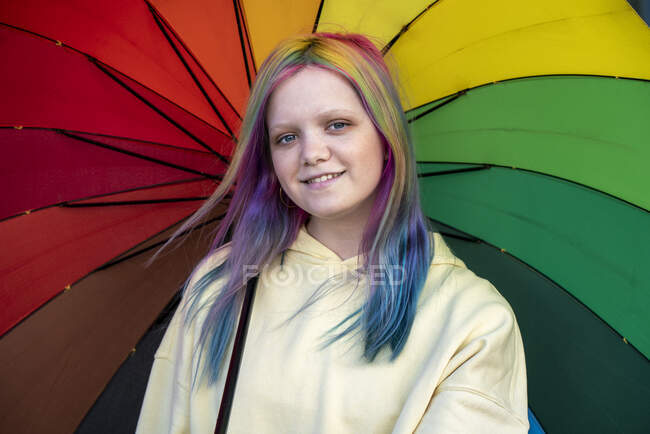 Portrait of young woman with dyed hair under umbrella — стокове фото