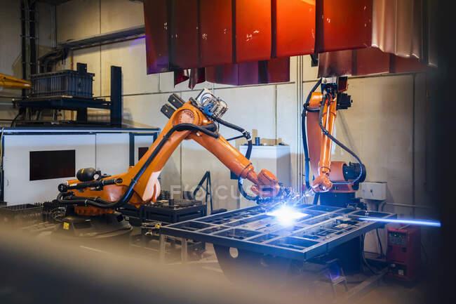 Помаранчеві роботизовані руки зварюють в промисловості — стокове фото