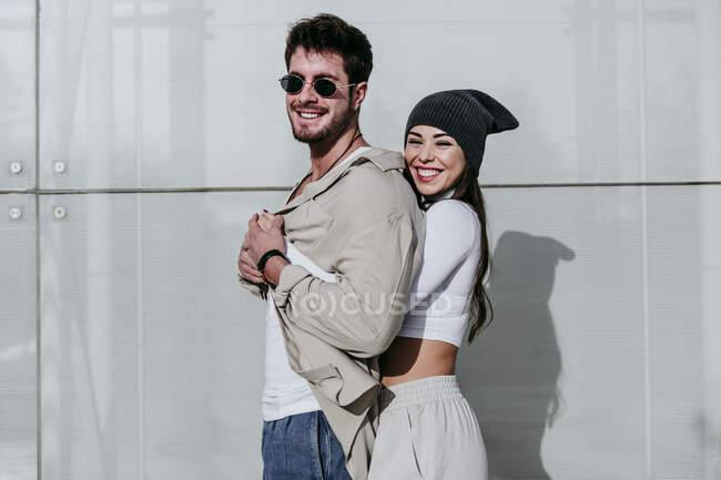 Улыбающаяся женщина обнимает партнера к стене в солнечный день — стоковое фото