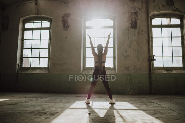 Sportswoman with hand raised exercising against window at abandoned factory — стоковое фото