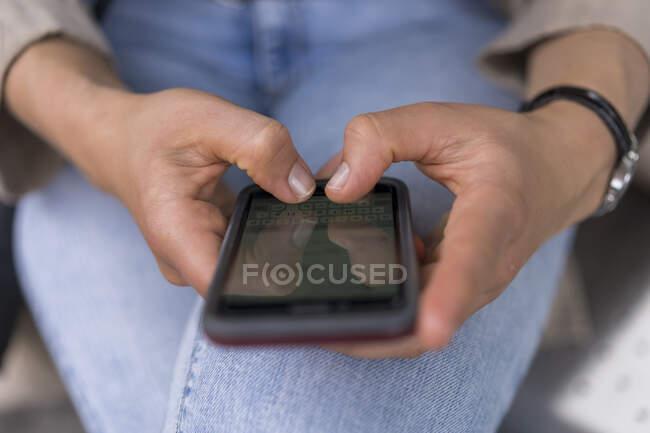 Manos de la mujer de mensajes de texto en el teléfono inteligente - foto de stock