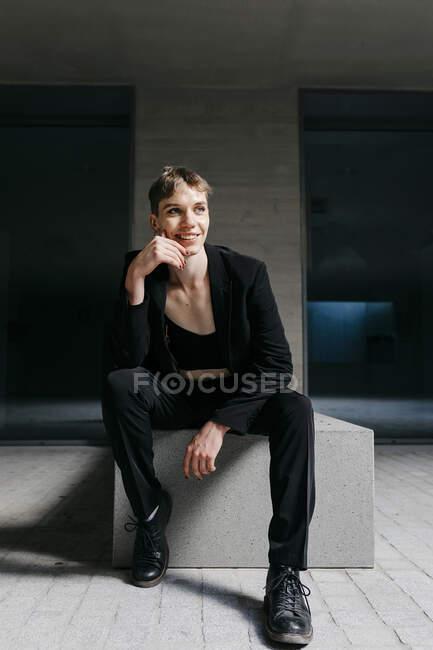 Вдумливий транс - молодий чоловік у чорному костюмі сидить на сидінні в підвалі. — стокове фото