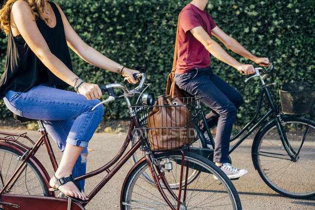 Couple riding bicycles on road against plants in park — Stock Photo