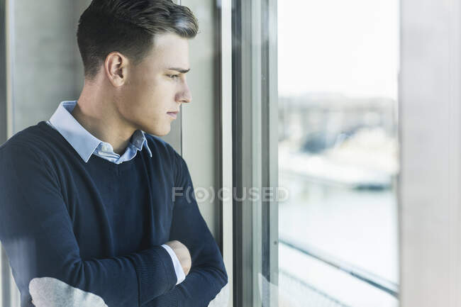 Thoughtful businessman with arms crossed looking through window in office seen through glass — Fotografia de Stock