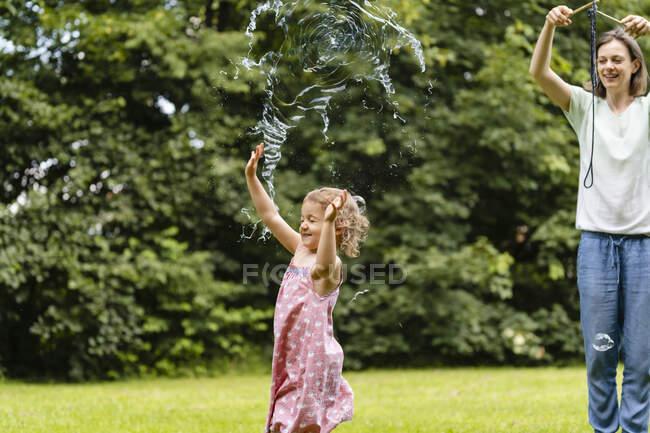 Menina explodindo bolha enquanto desfruta no parque público — Fotografia de Stock