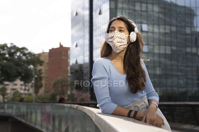Бизнесмен в защитной маске слушает музыку на наушниках, опираясь на перила — стоковое фото