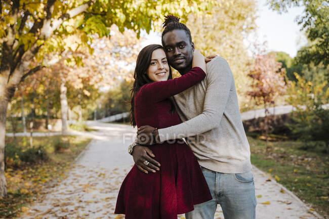 Улыбающаяся беременная женщина обнимает мужчину, стоя на тропинке в парке — стоковое фото