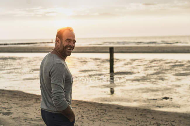Cheerful mature man standing against sea during sunset at weekend — Fotografia de Stock