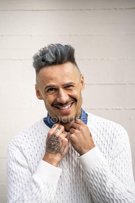 Sonriente hombre guapo con estilo con tatuaje contra la pared blanca - foto de stock