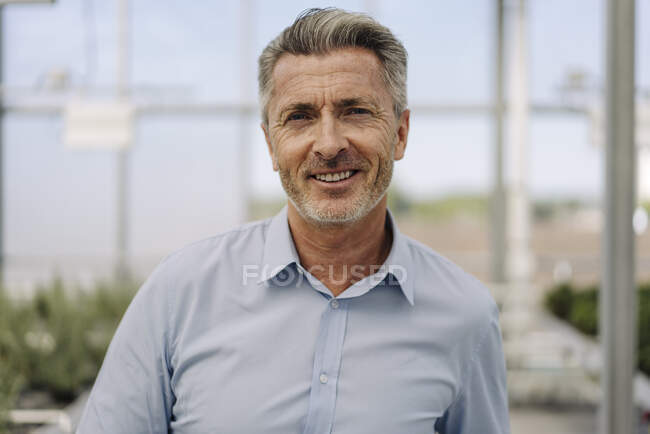 Зблизька усміхнений чоловік професійний працівник у розпліднику рослин. — стокове фото