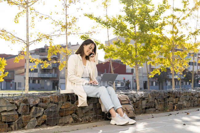 Female entrepreneur talking through smart phone while using laptop sitting on retaining wall — Stock Photo