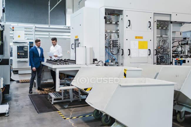 Коллеги по работе с документами, стоящие рядом с производственным оборудованием в промышленности — стоковое фото