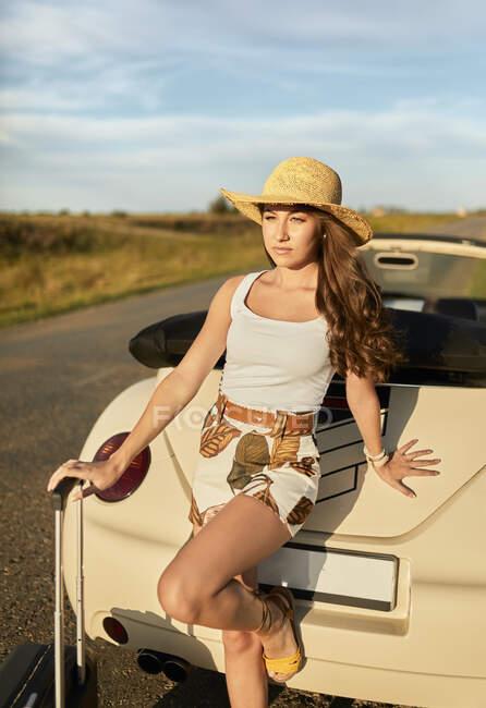 Giovane donna in piedi contro auto convertibile durante la giornata di sole — Foto stock