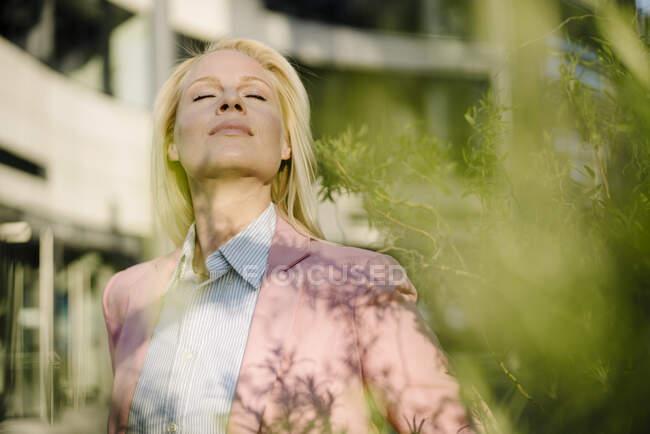 Блондинка-предприниматель с закрытыми глазами стоит в финансовом районе города — стоковое фото