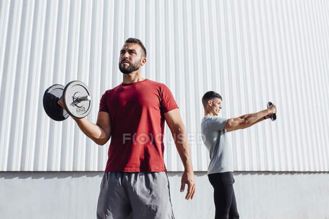 Молодые спортсмены, занимающиеся спортом, стоя у стены — стоковое фото