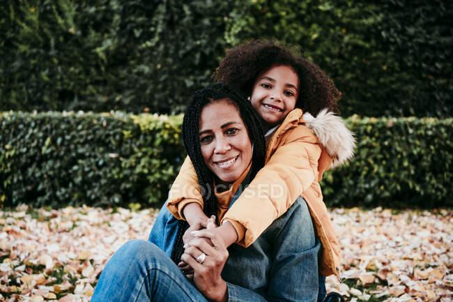 Sorridente ragazza abbracciando la madre da dietro mentre seduto al parco — Foto stock