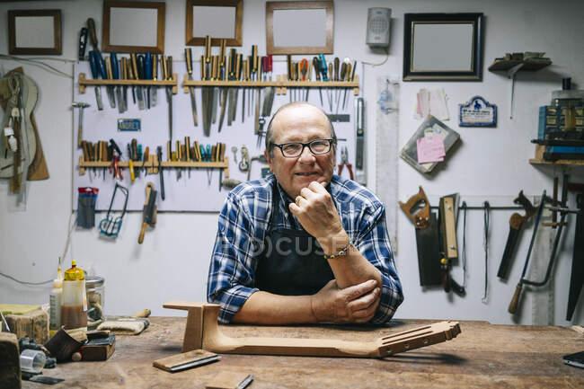 Lächelnder Mann mit Hand am Kinn steht an Werkbank in Werkstatt — Stockfoto