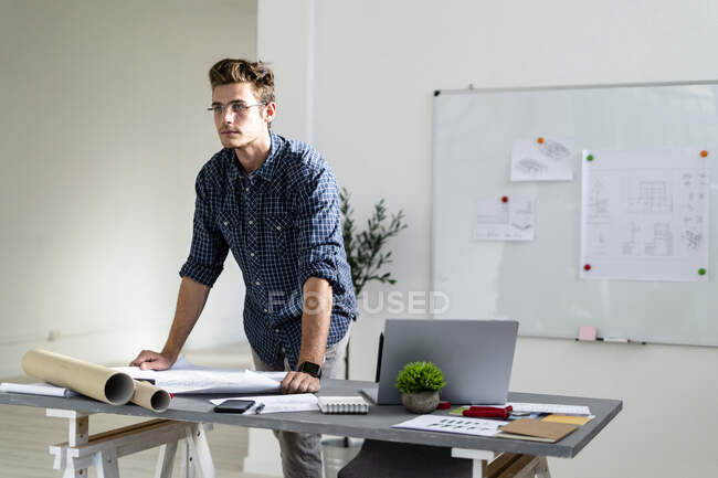 Man looking away while standing by desk at office — Stock Photo