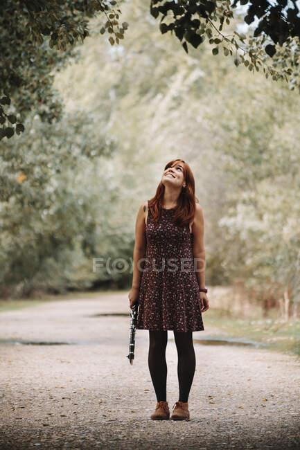 Sorridente giovane donna che tiene il clarinetto mentre guarda l'albero e in piedi sul sentiero nella foresta — Foto stock