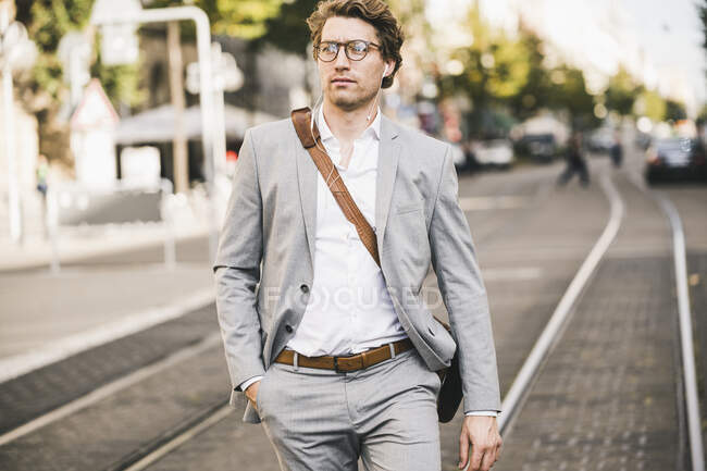 Handsome man with hands in pockets walking on tramway in city - foto de stock
