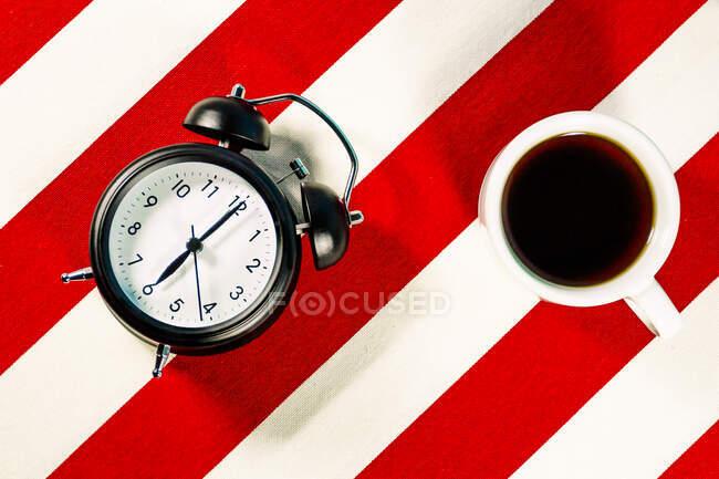 Taza de café y despertador en blanco y rojo patrón de rayas - foto de stock