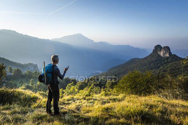 Hombre con mochila usando teléfono móvil de pie en la montaña durante el amanecer, Orobie, Lecco, Italia - foto de stock