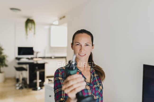 Mujer sonriendo mientras juega con taladro eléctrico en casa - foto de stock