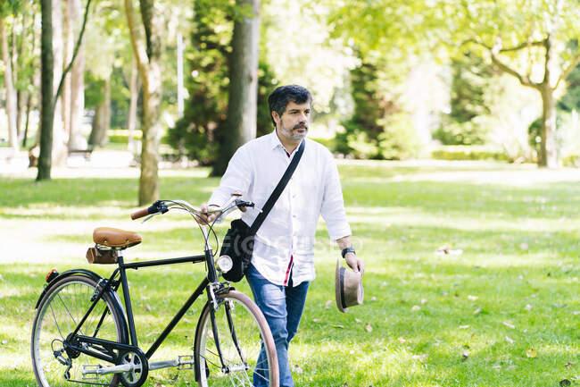 Homem maduro com bicicleta andando na grama no parque público — Fotografia de Stock