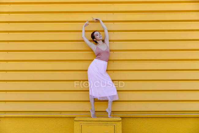 Ballerina with arms raised posing while standing on seat against yellow wall — стокове фото