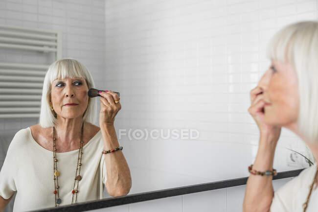 Mulher sênior aplicando maquiagem enquanto olha no espelho em casa — Fotografia de Stock