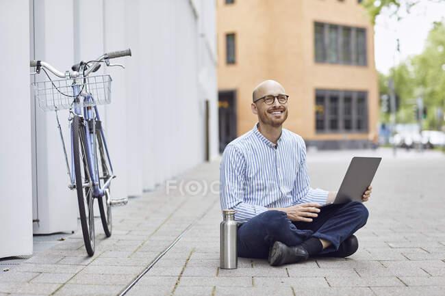 Souriant milieu homme adulte en utilisant un ordinateur portable tout en étant assis dans la rue — Photo de stock
