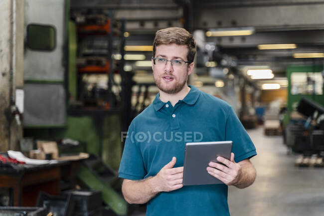 Male worker with digital tablet standing in factory — Stock Photo