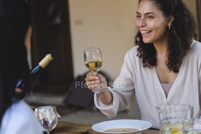 Улыбающаяся женщина, держащая бокал вина, глядя на друга, сидящего за обеденным столом на заднем дворе — стоковое фото