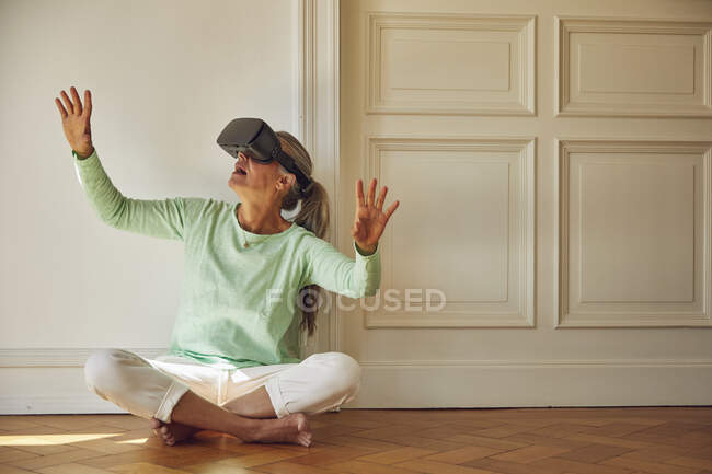 Woman using VR glasses while sitting on hardwood floor at home — Stock Photo