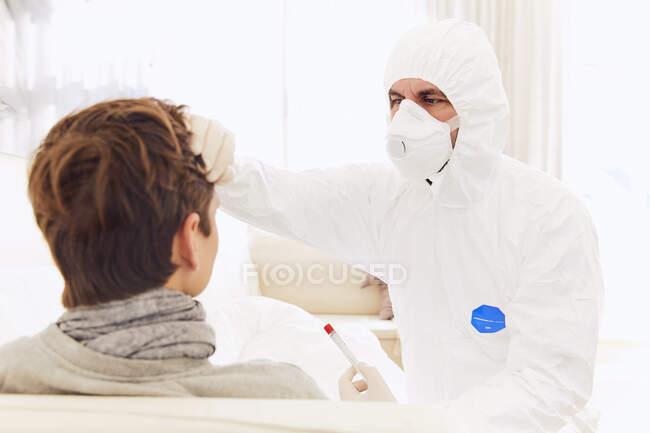 Doctor vistiendo traje protector examinando a un joven en casa - foto de stock