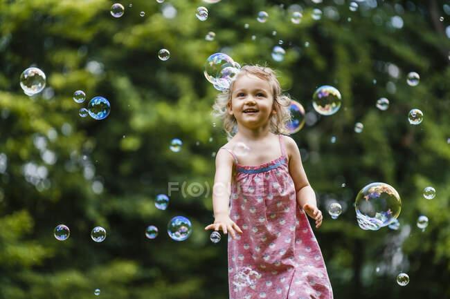 Счастливая девушка наслаждается во время бега среди пузырей в парке — стоковое фото