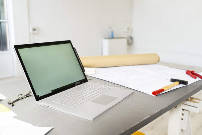 Laptop and architectural blueprint lying on desk in studio — Stock Photo