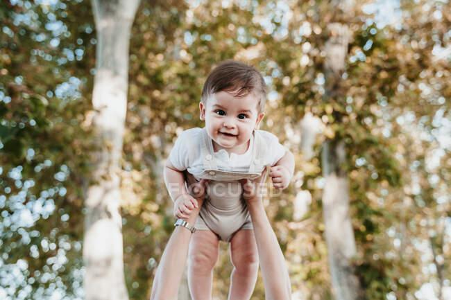 Мать руки поднимает ребенка на открытом воздухе — стоковое фото