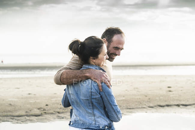 Cheerful mature couple standing at beach against sky during weekend - foto de stock
