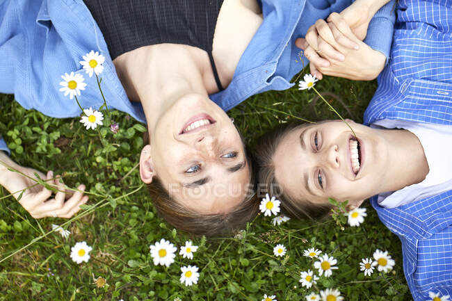 Close-up of cheerful female friends lying by flowers on grassy land in garden — Stock Photo