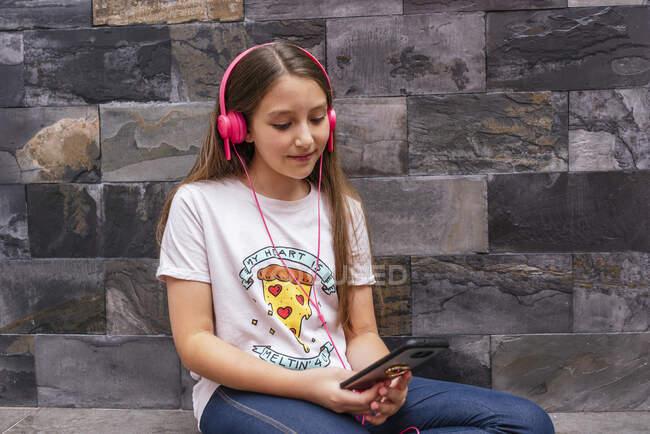 Ragazza carina con le cuffie utilizzando il telefono cellulare mentre seduto contro il muro a casa — Foto stock