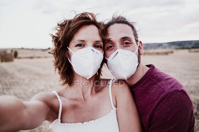 Hombre y mujer usando mascarilla de pie en el campo durante COVID-19 - foto de stock