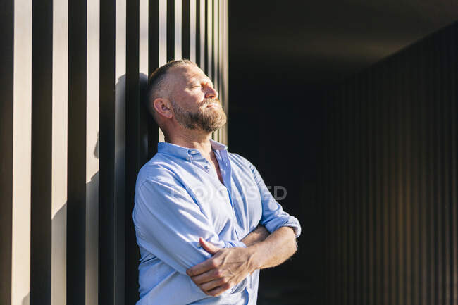 Businessman with arms crossed leaning on wall — Stock Photo