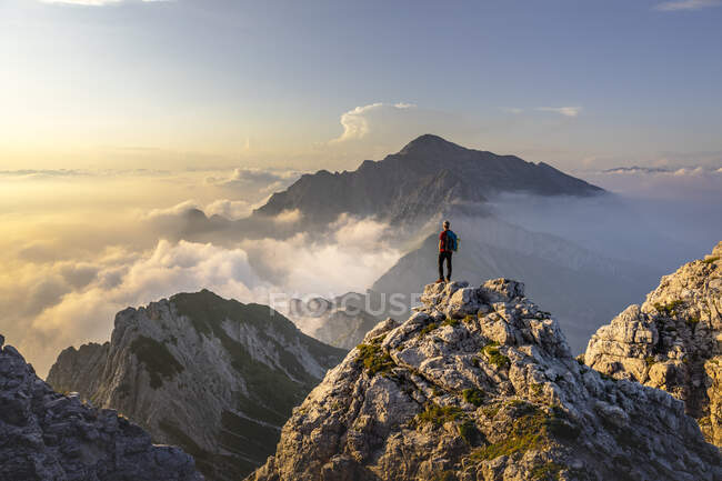 Hiker admiring awesome view while standing on mountain peak at Bergamasque Alps, Italy — Stock Photo