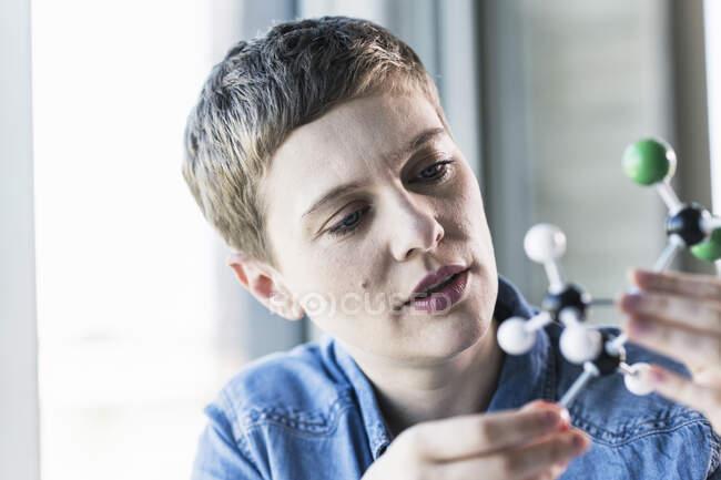 Woman looking at molecule model — Stock Photo