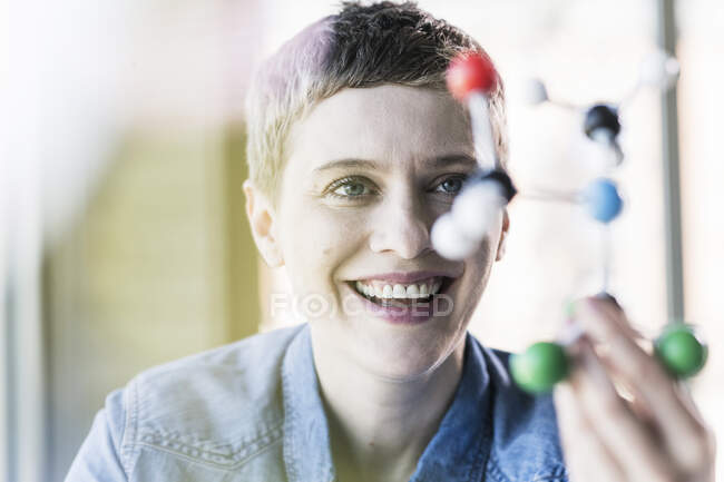 Happy woman looking at molecule model — Stock Photo