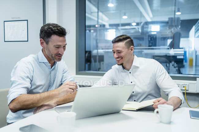 Smiling businessman with male coworker working on laptop in board room at factory — Stock Photo