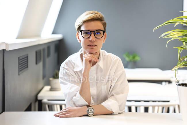 Schöne blonde Geschäftsfrau mit der Hand am Kinn sitzt am Schreibtisch in Büro-Cafeteria — Stockfoto