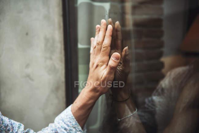 Primer plano de un par de manos tocándose a través de la ventana de la cafetería - foto de stock