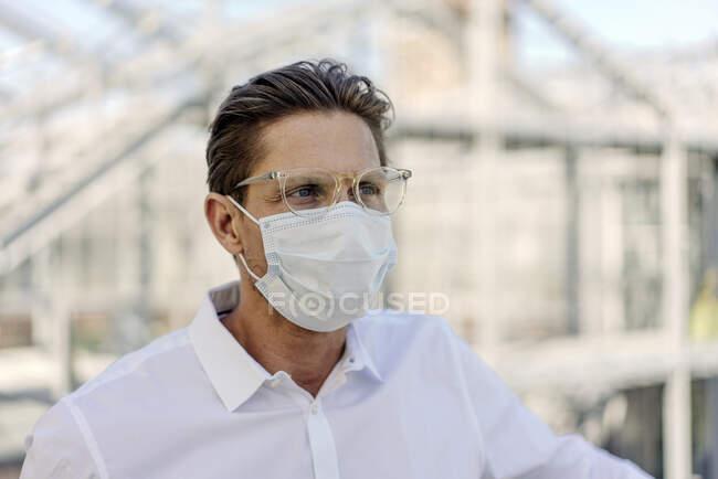 Primer plano del hombre de negocios con mascarilla mirando hacia otro lado en invernadero - foto de stock